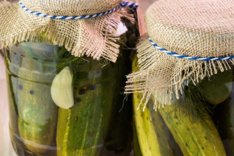 Jars of pickle juice covered with burlap lids.