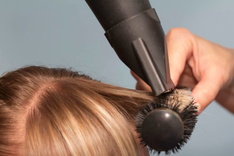 stylist drying hair with round brush