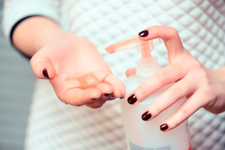 woman putting moisturizer on hands