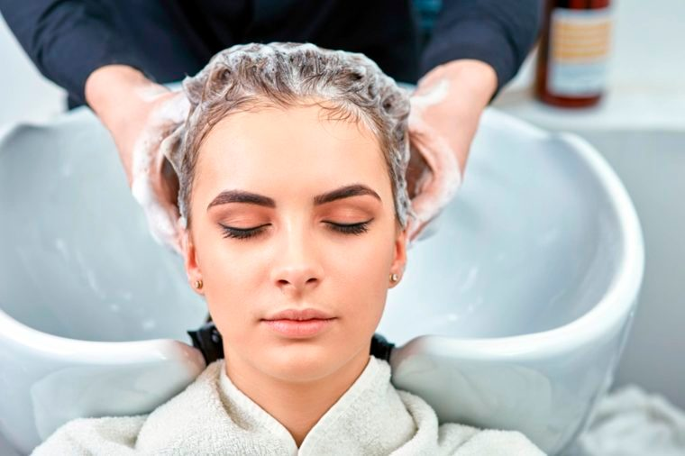 stylist shampooing woman's hair