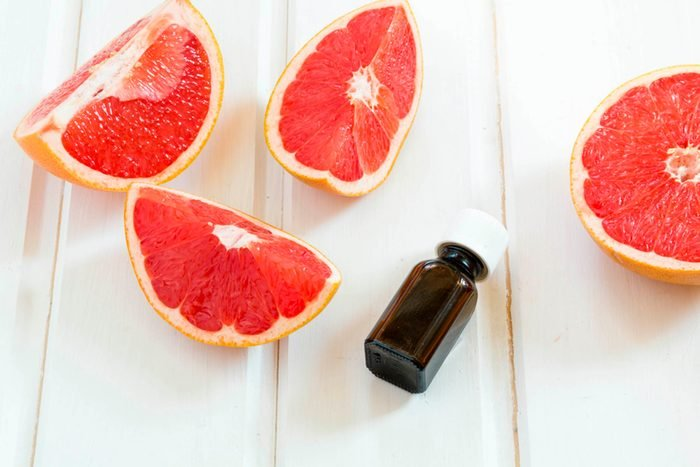 ruby grapefruit slices with essential oil bottle