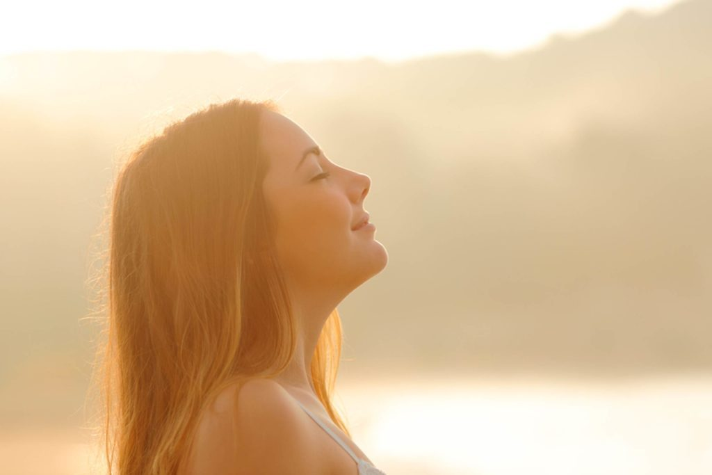 Woman outdoors, smiling in the sunlight with her eyes closed