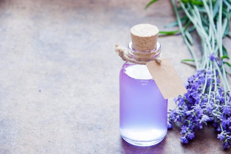 lavender oil in a clear bottle and lavender flowers on a table
