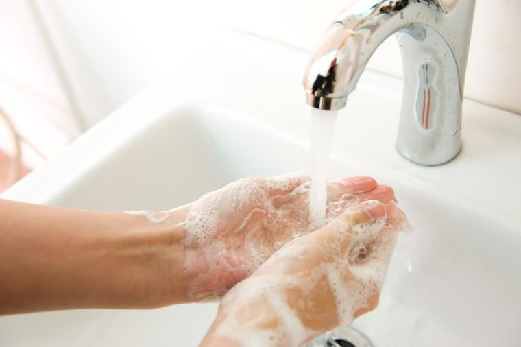 soapy hands in a sink under a faucet
