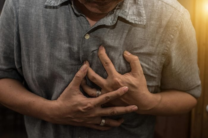 man clutching chest, having heart attack