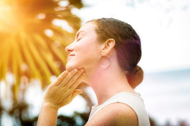 woman rubbing lotion on her neck