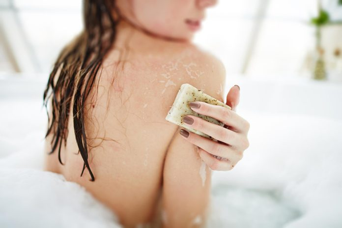 Woman using soap in a bubble bath.