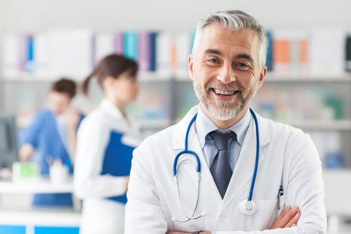 smiling grey-haired doctor in white coat with blue stethoscope