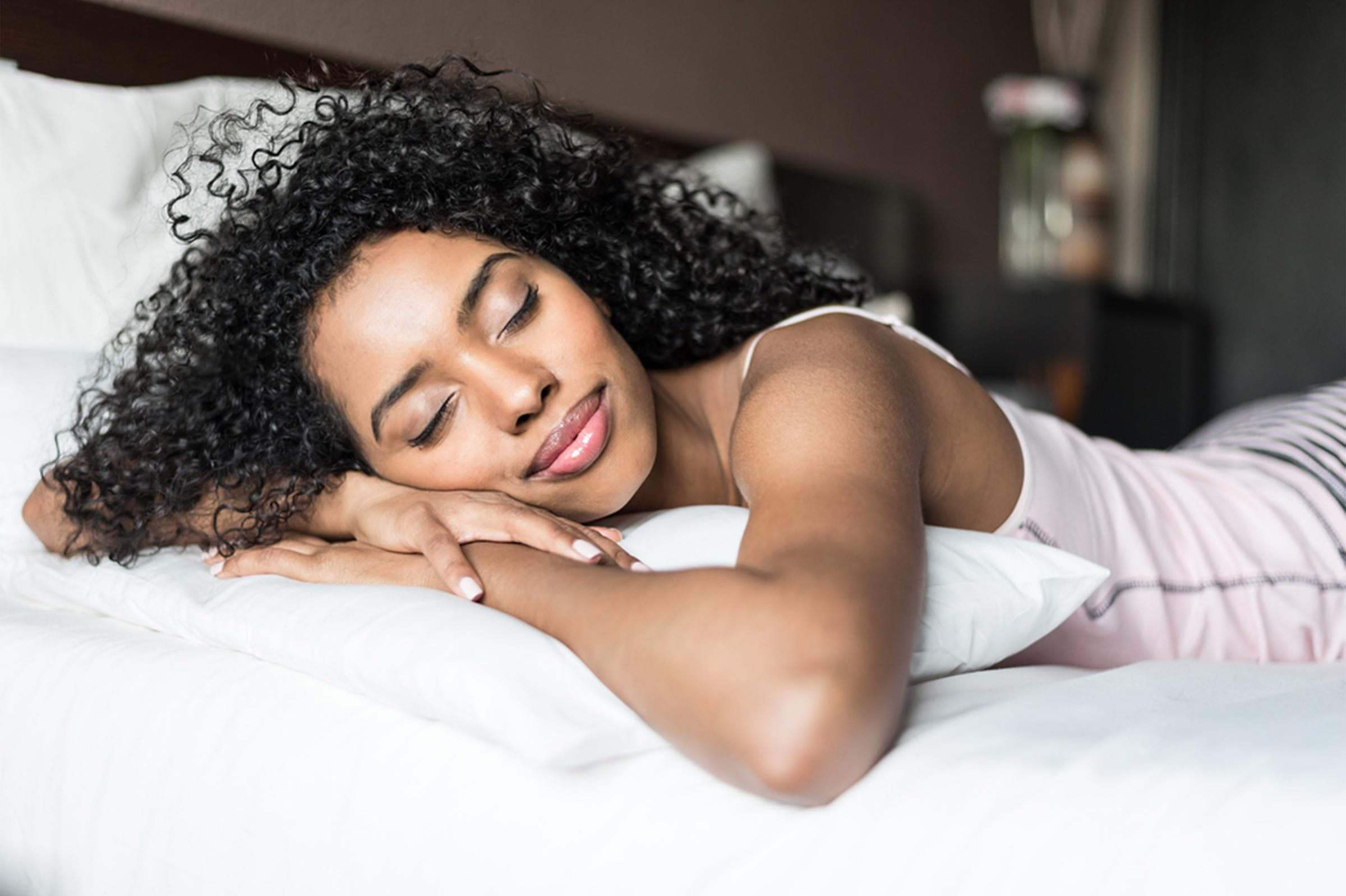 woman sleeping on stomach with smile on her face
