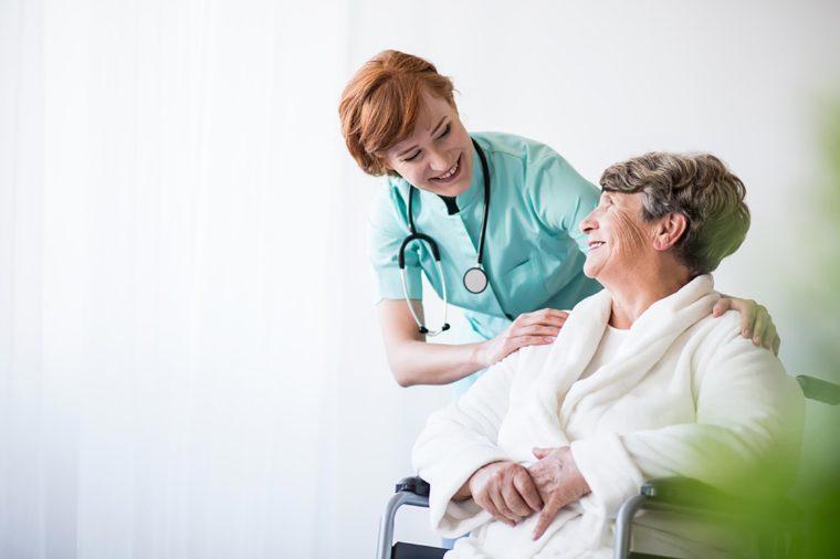 nurse talking with woman in wheelchair