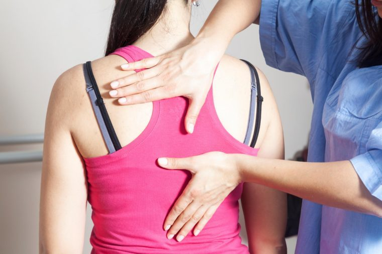 doctor checking woman's spine