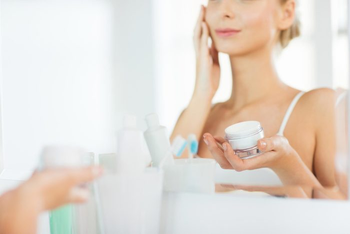 woman looking into the mirror and applying Moisturizer