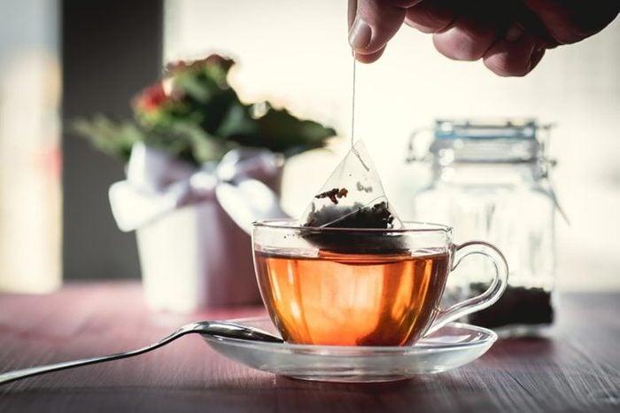 close up os a cup of tea in a clear cup with a hand holding a tea bag