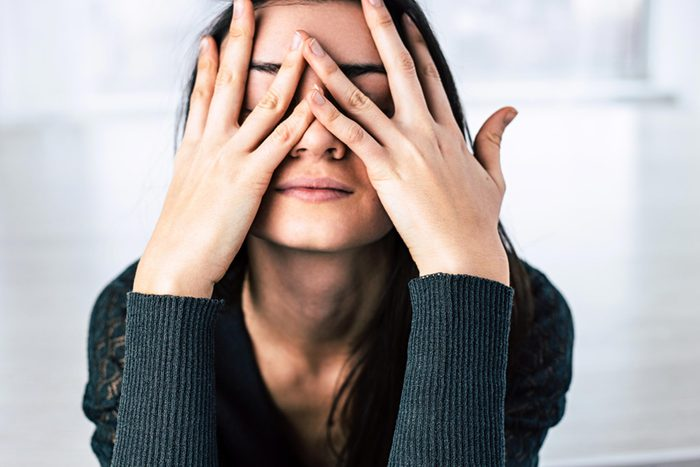 woman pressing her hands to her face