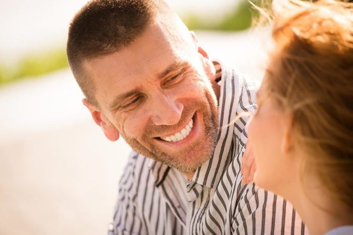 man smiling at a woman outdoors