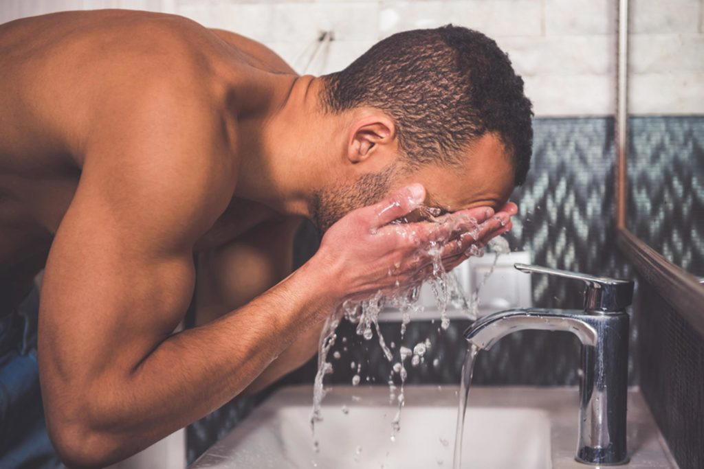 Man washing his face.