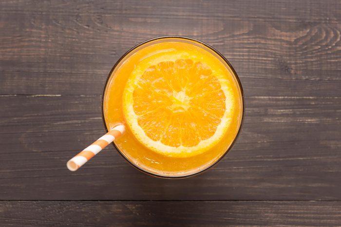 glass of orange juice with orange slice and straw