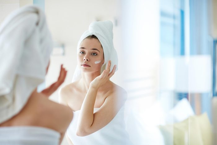 woman with towel wrapped around her head applying face cream