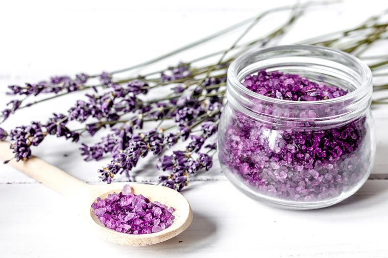 lavender stems on a white surface next to a wooden spoon and clear jar holding lavender petals