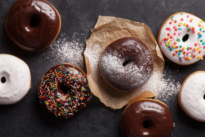 Chocolate-glazed doughnuts, some with sprinkles, on a table