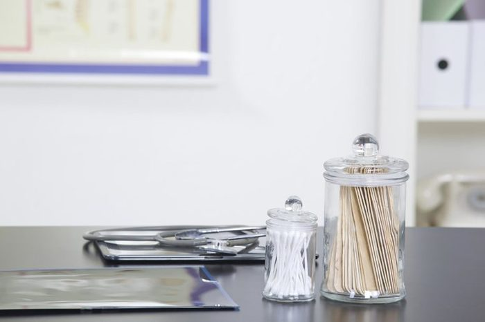 a doctor's office counter with swabs, tongue depressors, and stethoscope