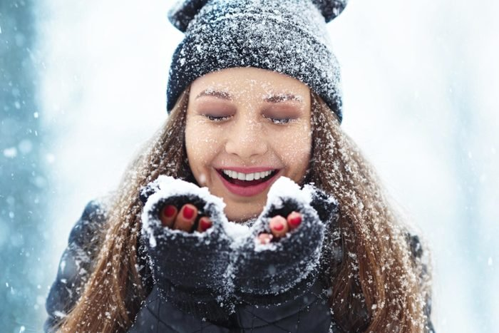 woman in winter clothes catching snow