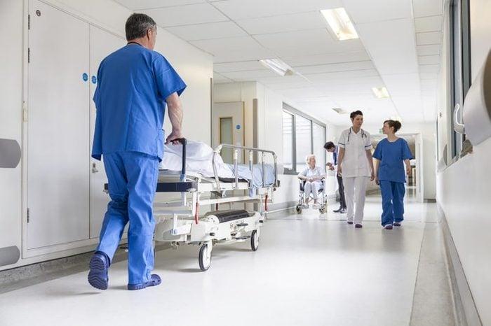 a hospital corridor with doctors, nurses, and patients