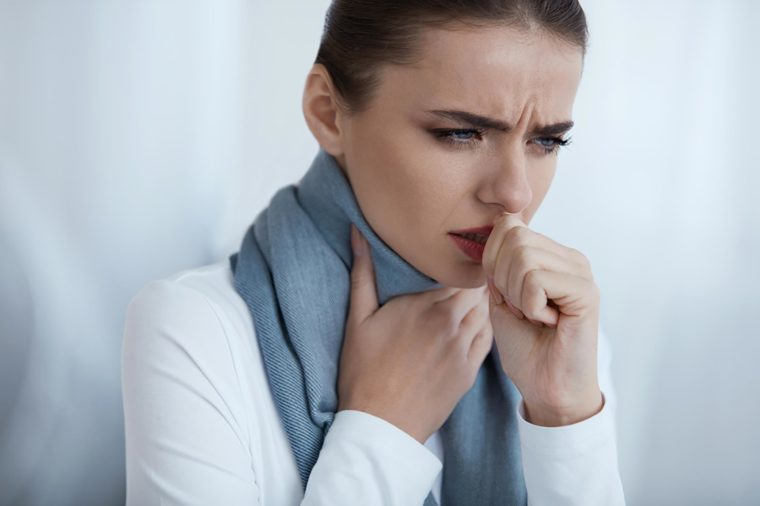 woman coughing and scarf around throat