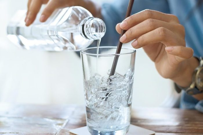 person pouring water into glass with ice and straw