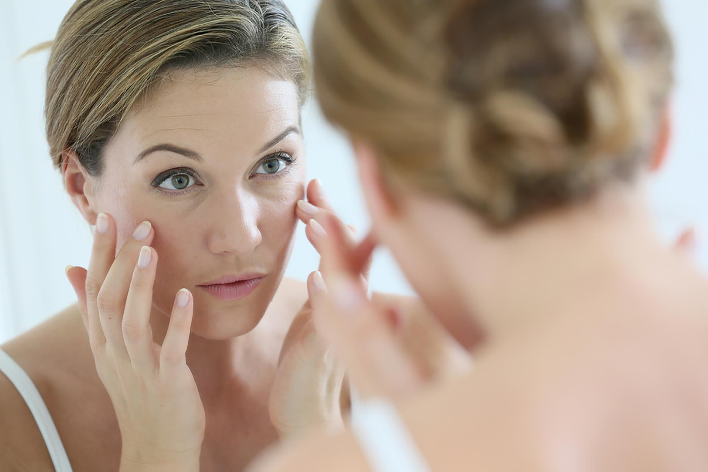 Woman looking at face in the mirror