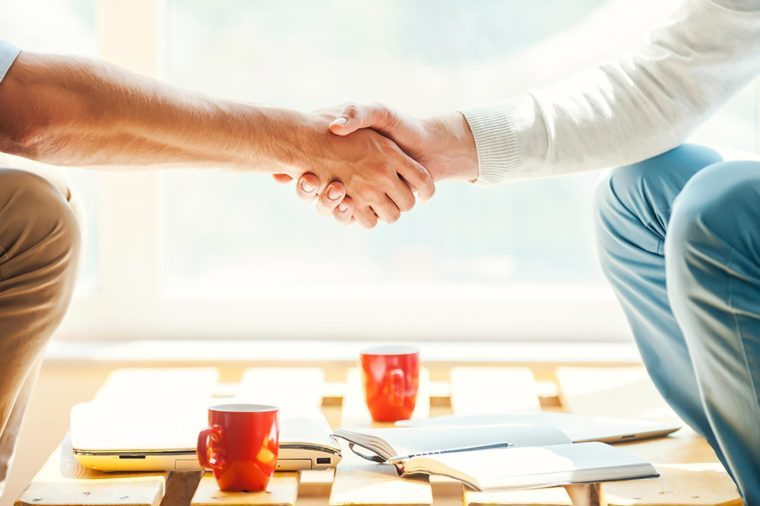 two people shaking hands over a table