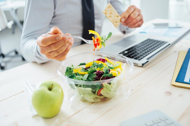 business man eating a salad at his desk