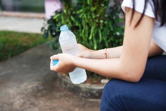 woman sitting outside holding an open plastic water bottle