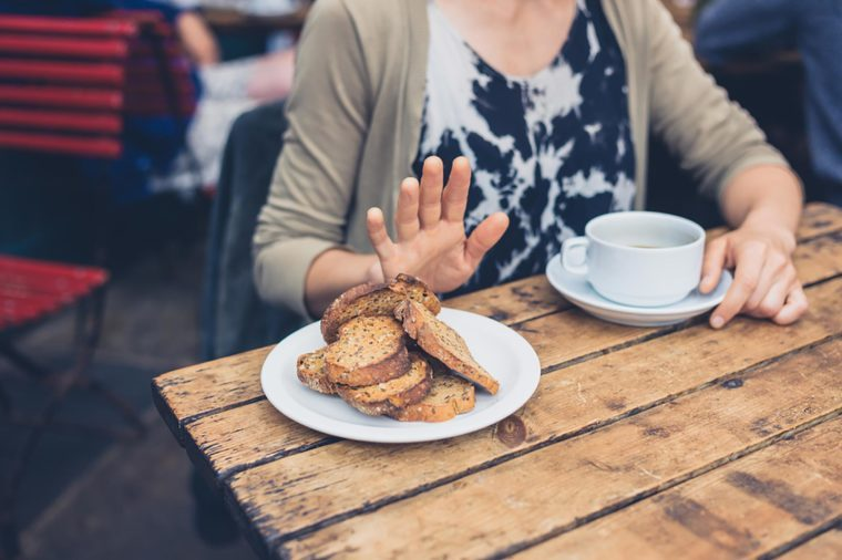 woman at breakfast holding her hand up to toast