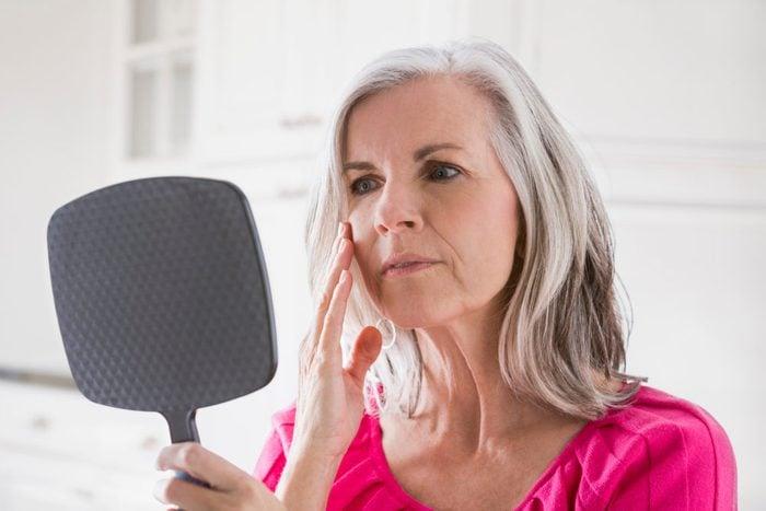 woman looking in handheld mirror