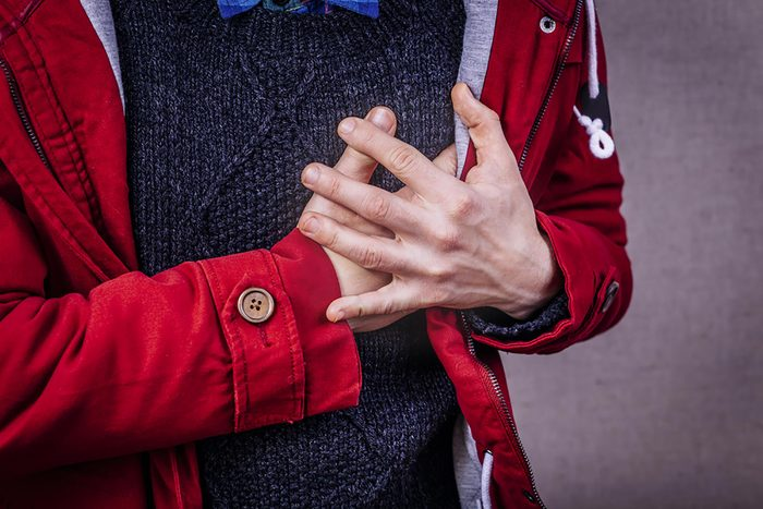 man in a sweater and jacket clutching his chest