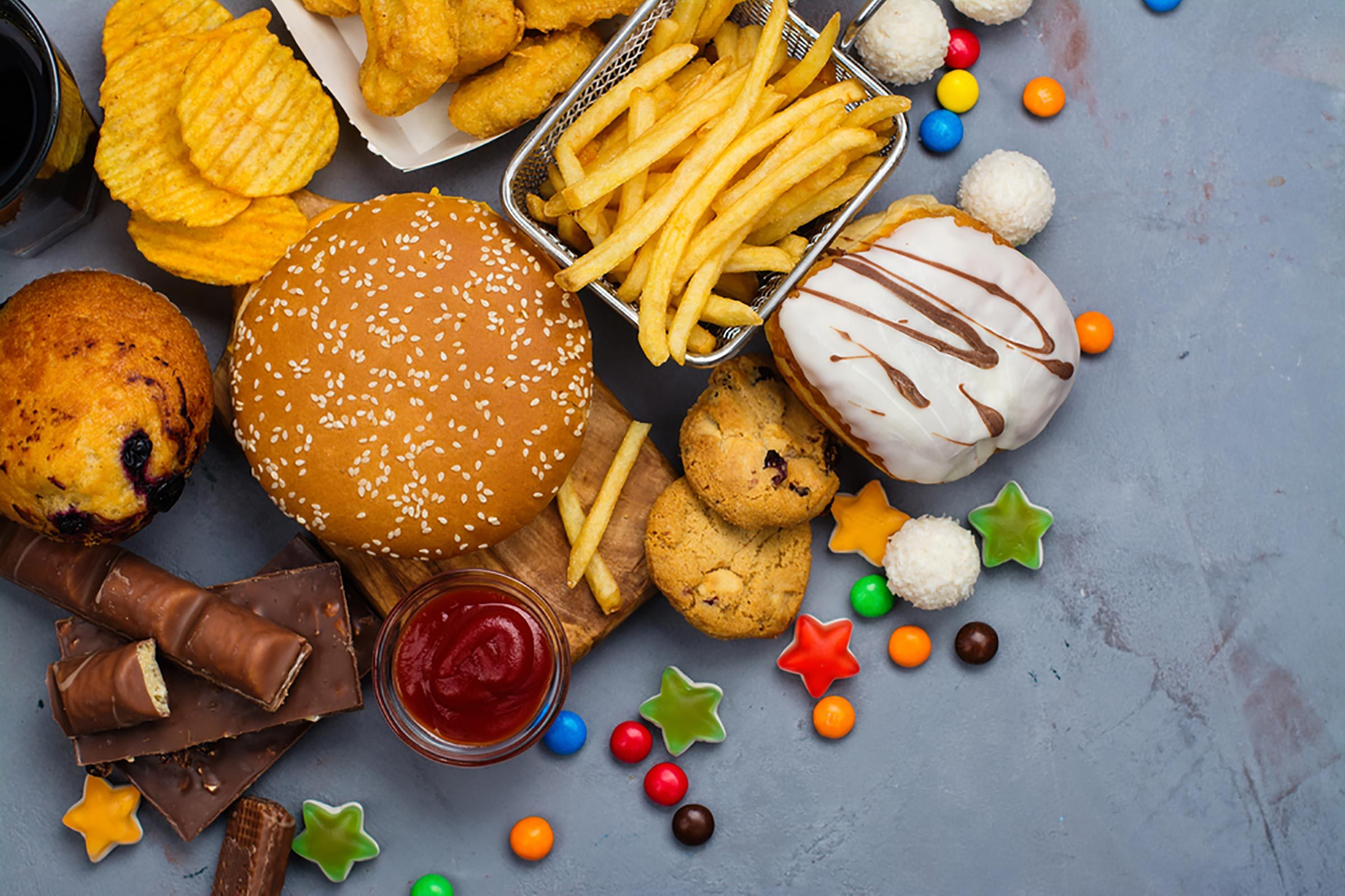 a variety of junk food: fries, burger, chips, candy, cookies