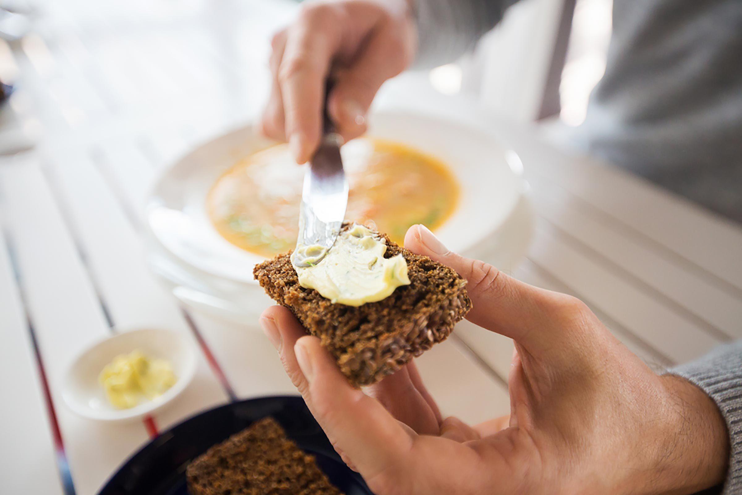 Man putting margarine on toast