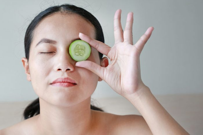 woman and cucumber on eyes dark circles