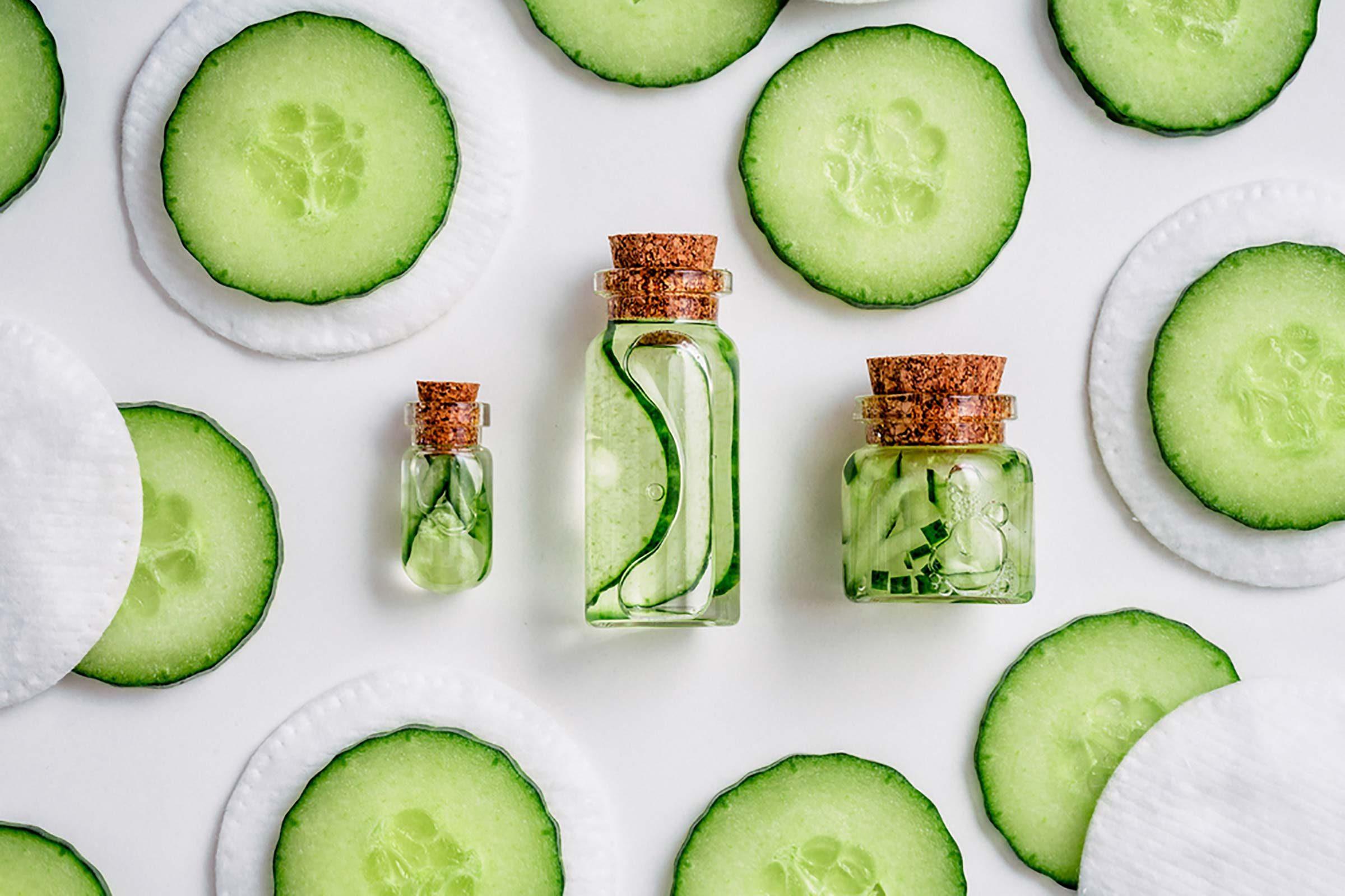 Cucumber slices artfully arranged around jars containing cucumber liquid