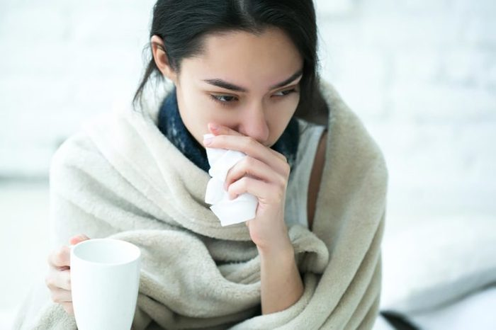 woman bundled up with tea holding a tissue
