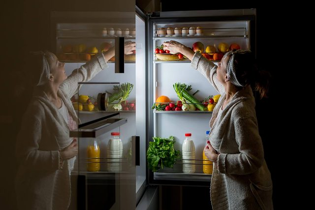 woman at open refrigerator snacking at night