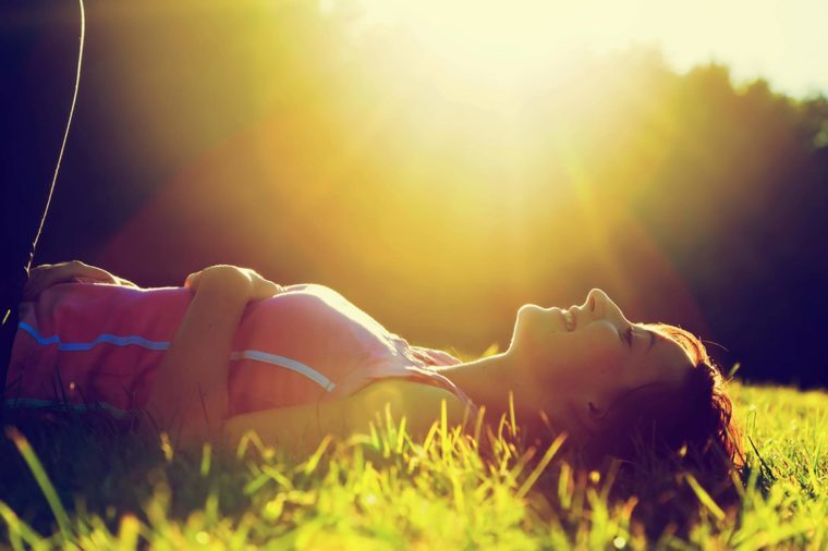 A woman lying in the grass outdoors in the sunlight.
