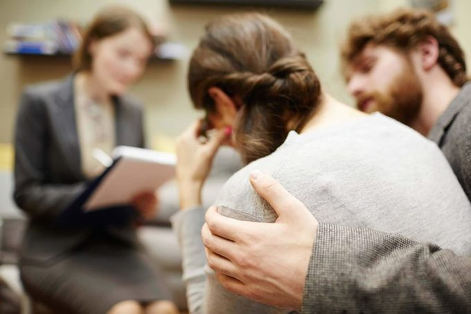 man comforting a woman in front of a therapist