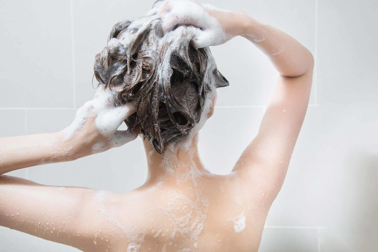 Woman shampooing her hair in the shower.