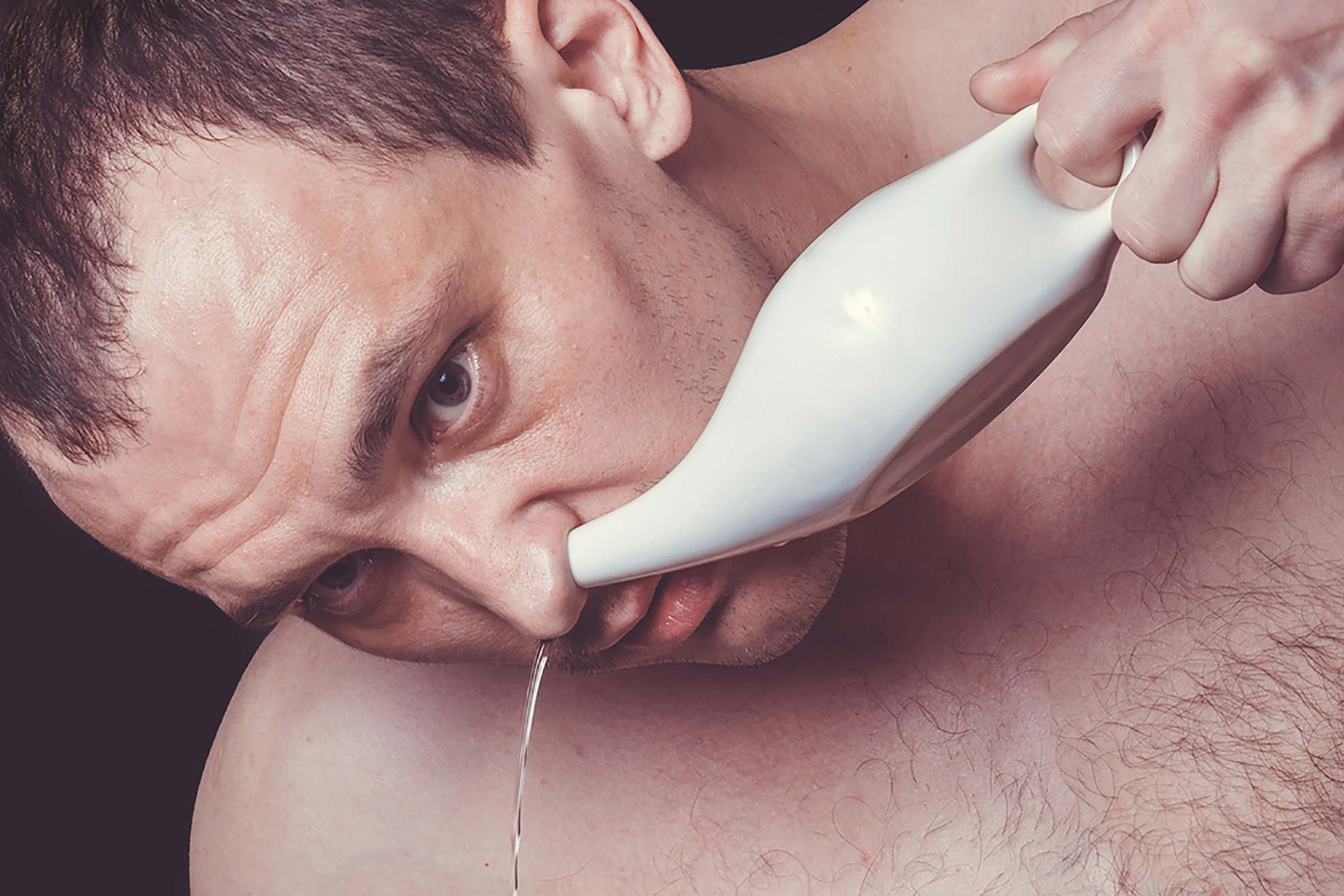 Man using a neti pot in his nostril.