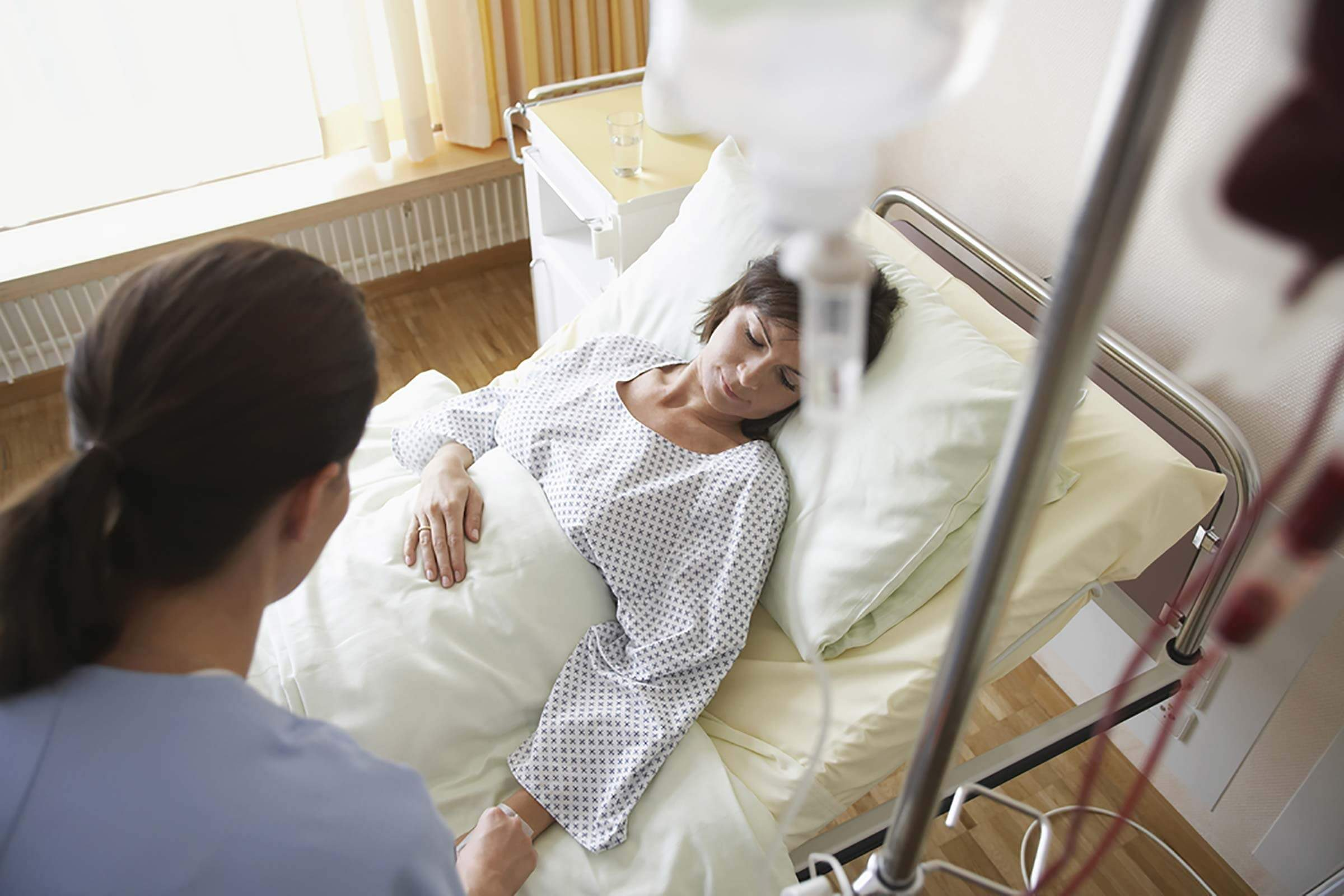 Woman lying in a hospital bed with an IV drip.
