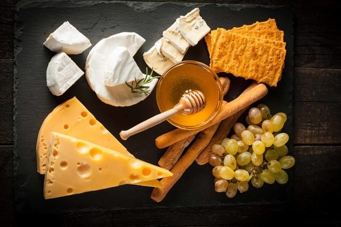 varieties of cheese with crackers, honey, and grapes