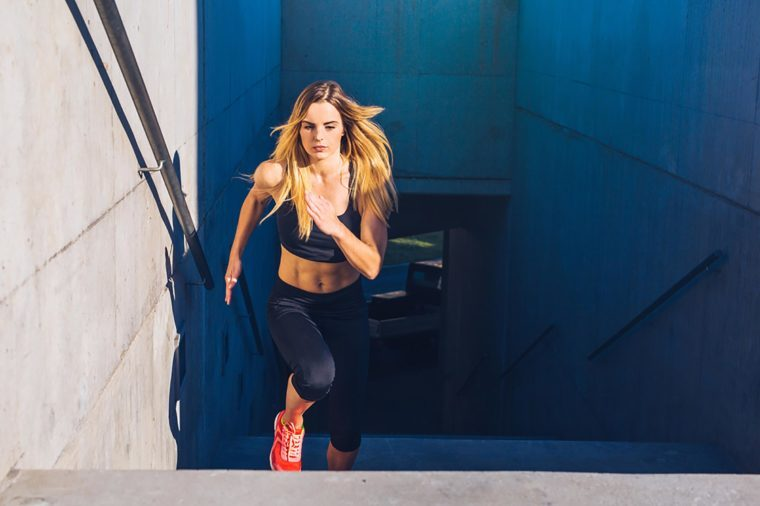 Woman in exercise gear jogging up stairs.