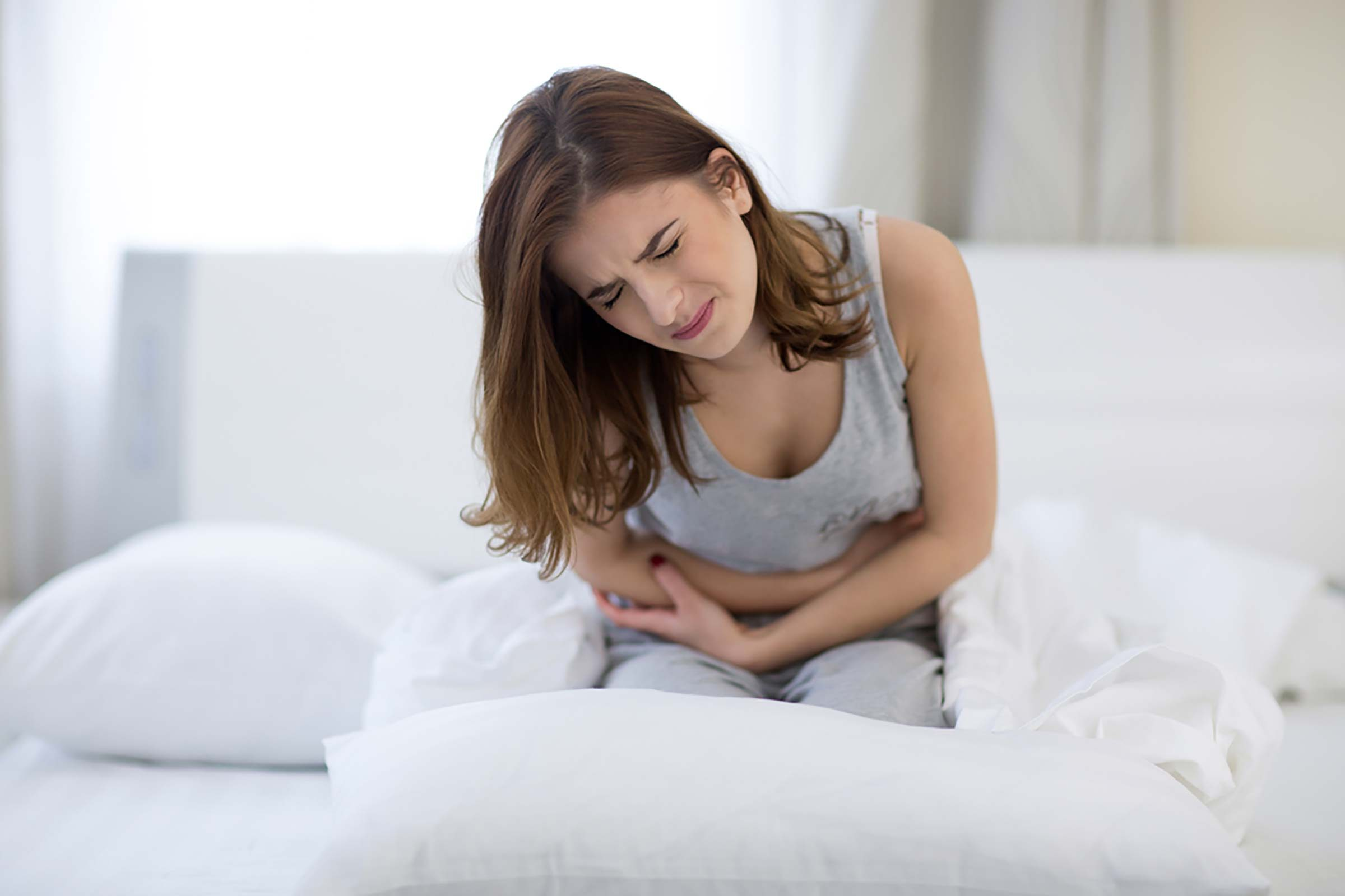 woman doubled over in pain in bed